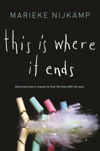 """Image shows the cover of This Is Where It Ends: a black background with four colored pieces of chalk, being shot to bits. The tagline reads: """"Everyone has a reason to fear the boy with the gun."""""""