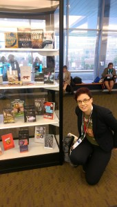 Photo of Marieke, crouching next to a display case full of books, including This Is Where It Ends, at ALA Midtwinter, 2016.
